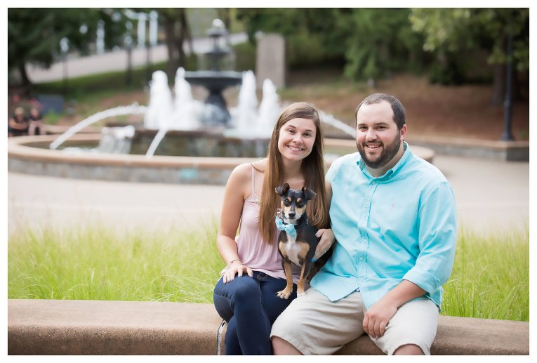 man and a woman sitting in front of a fountain with a dog